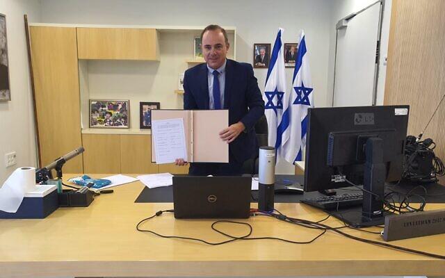 Le ministre israélien de l'Energie, Yuval Steinitz, pose avec une copie des statuts du EastMed Gas Forum (EMGF), signés par Israël, l'Egypte, la Jordanie, la Grèce, Chypre, l'Italie et l'Autorité palestinienne, le 22 septembre 2020. (Ministère de l'Energie)