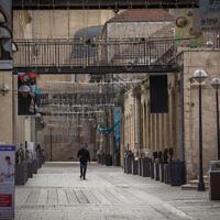 Des gens passent devant des magasins fermés dans le centre commercial vide de Mamilla à Jérusalem, lors d'un confinement dû au COVID-19, le 23 mars 2020. (Nati Shohat/Flash90)