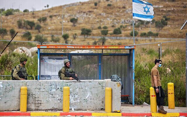 Des soldats de Tsahal gardent une station de bus à la jonction Tapuah, à côté de la ville de Naplouse en Cisjordanie, le 30 juin 2020. (AP/Oded Balilty)