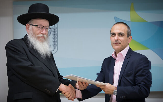 Le vice-ministre de la Santé Yaakov Litzman, (à gauche), serre la main de Ronni Gamzu lors d'une conférence de presse au ministère de la Santé à Jérusalem le 3 janvier 2019. (Noam Revkin Fenton/Flash90)