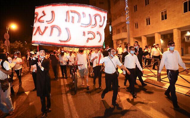 """Des hassidim de Breslev protestent à Jérusalem contre le Premier ministre Benjamin Netanyahu au sujet de l'interdiction faite aux voyageurs étrangers par l'Ukraine, qui les empêchera de se rendre à Ouman pour le Rosh Hashanah, 29 avril 2020. Le panneau dit : """"Netanyahu contre Rabbi Nahman."""" (Yonatan Sindel/Flash90)"""