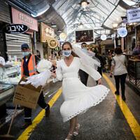 Une mariée israélienne avec un masque facial se promène au marché Mahane Yehuda à Jérusalem le 15 septembre 2020. (Yonatan Sindel/Flash90)