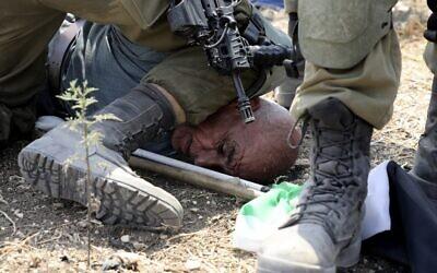 Des soldats israéliens arrêtent un manifestant palestinien lors d'une manifestation contre l'expansion des implantations israéliennes dans le village de Choufa, au sud-est de Tulkarm en Cisjordanie occupée, le 1er septembre 2020. (Photo de JAAFAR ASHTIYEH/AFP)
