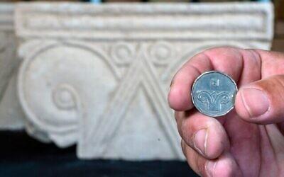 Une pièce de cinq shekels juxtaposée à une tête de colonne trouvée à Armon HaNatziv (Yaniv Berman, Autorité des antiquités d'Israël)