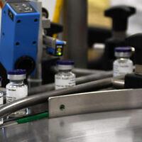 Des flacons d'un éventuel vaccin contre le coronavirus sur une chaîne de montage, à l'Institut israélien de recherche biologique, le 25 octobre 2020. (Crédit : Ministère de la défense)