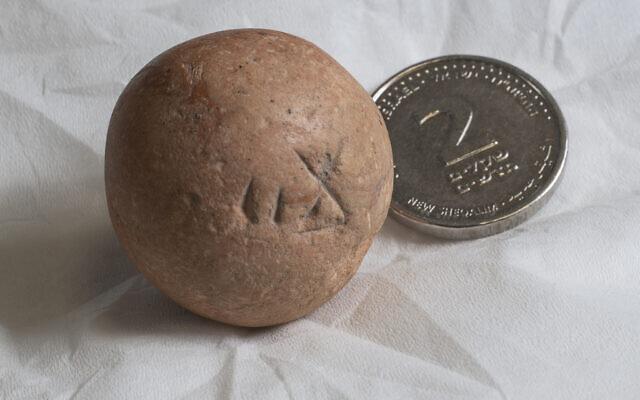 Le poids en pierre de calcaire de deux shekels, vieux de 2700 ans, à côté d'une pièce contemporaine de deux shekels (Crédit :  Shai Halevi, Autorité israélienne des antiquités)