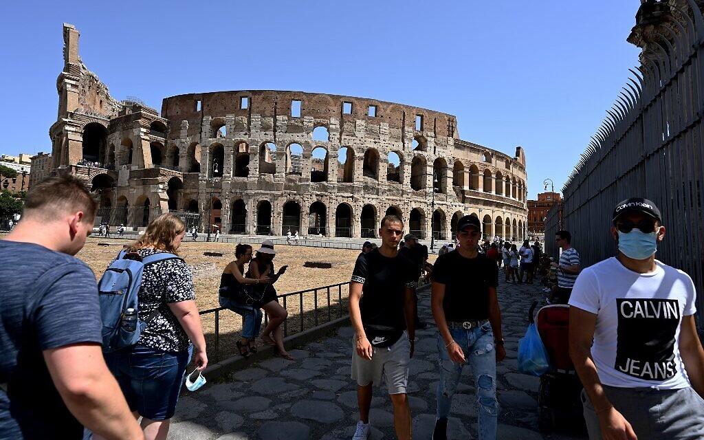 Des touristes, dont certains portent un masque facial, se promènent près du monument du Colisée, le 22 août 2020 à Rome, lors de l'épidémie de COVID-19. (Vincenzo PINTO / AFP)