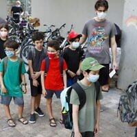 Des parents israéliens accompagnent leurs enfants pour le premier jour d'école, lors de la pandémie de coronavirus, à Tel Aviv le 1er septembre 2020. (JACK GUEZ / AFP)
