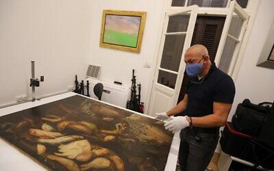 Gaby Maamary, spécialiste libanais de la conservation des œuvres d'art, examine un tableau du XVIIe siècle de la peintre italienne Elena Recco, endommagé lors de l'explosion du port de Beyrouth, dans son atelier de la capitale, le 17 septembre 2020. (ANWAR AMRO / AFP)
