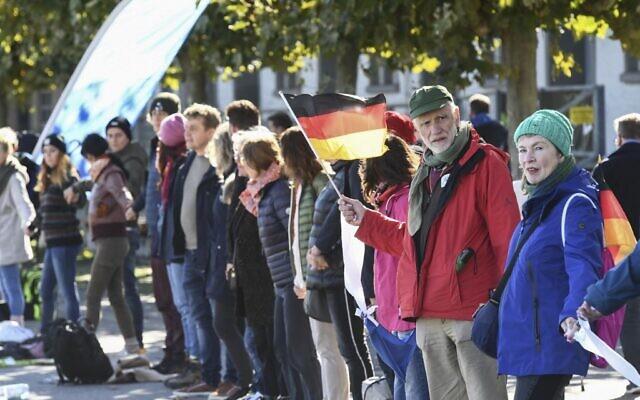 Des citoyens participent à une chaîne humaine pour protester contre le port du masque et les restrictions liés à la pandémie de coronavirus à Constance, dans l'ouest de l'Allemagne, le 3 octobre 2020. (SEBASTIEN BOZON / AFP)