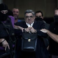 L'ancien député et chef du parti Aube dorée, Nikolaos Michaloliakos escorté par la police, à Athènes, le 28 septembre 2013.(Crédit :ANGELOS TZORTZINIS / AFP)