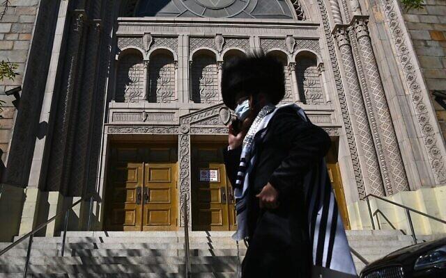 Un Juif hassidique devant une synagogue fermée à Borough Park à Brooklyn, l'un des cinq arrondissements de New York, le 9 octobre 2020. (Crédit : Angela Weiss / AFP)