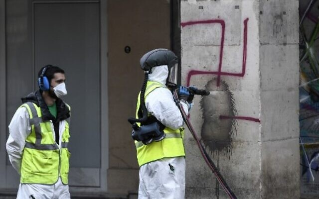 Des employés municipaux nettoient des croix gammées sur les arcades de la rue de Rivoli à Paris, le 11 octobre 2020. (Crédit : STEPHANE DE SAKUTIN / AFP)
