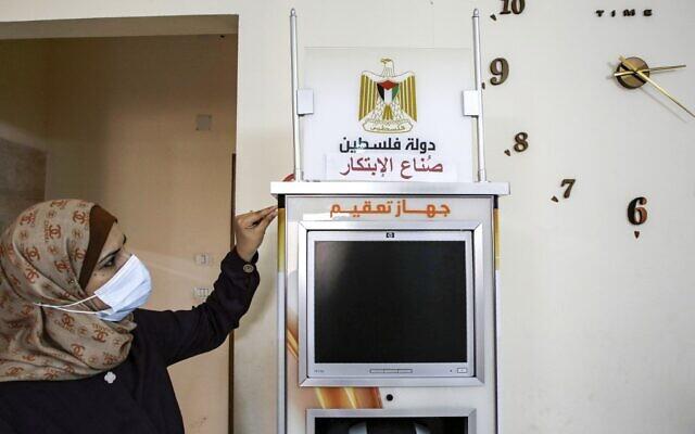 La femme d'affaires palestinienne Heba al-Hindi présente un dispositif de stérilisation intelligent conçu et fabriqué localement dans la ville de Gaza, le 8 octobre 2020, alors que la machine doit être déployée dans diverses installations de la zone dans le cadre des efforts visant à freiner la propagation de la COVID-19. (Crédit : MOHAMMED ABED / AFP)