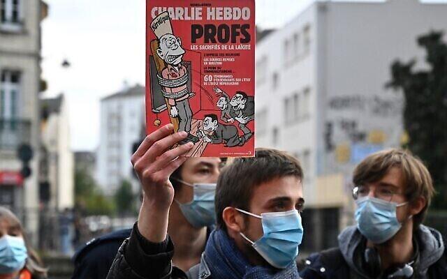 Un homme tient une édition du magazine Charlie Hebdo lors d'une manifestation à Rennes le 17 octobre 2020, un jour après la décapitation d'un enseignant à Conflans-Sainte-Honorine, à 30 km au nord-ouest de Paris, lors d'une attaque terroriste islamiste. (Damien MEYER / AFP)