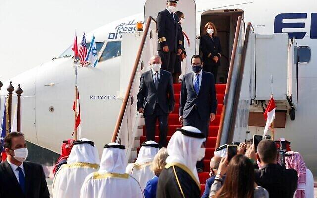 Le conseiller israélien à la sécurité nationale Meir Ben-Shabbat, à gauche, et le secrétaire d'Etat américain au Trésor Steve Mnuchin à leur descente de l'avion à l'aéroport international du Bahreïn, le 18 octobre 2020. (Crédit : Ronen Zvulun/Pool/AFP)