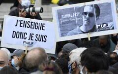 Des manifestants tiennent une pancarte indiquant « J'enseigne donc je suis » et un portrait du professeur d'histoire Samuel Paty alors qu'ils se rassemblent place de la République à Paris le 18 octobre 2020, deux jours après avoir été décapité par un agresseur abattu par les policiers. (Crédit : Bertrand GUAY / AFP)