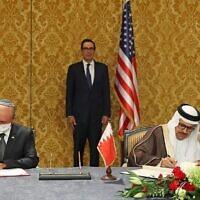Le chef de la délégation israélienne, le conseiller à la sécurité Meir Ben-Shabbat, à gauche, et le ministre bahreïni des Affaires étrangères,  Abdullatif bin Rashid Al-Zayani, signent l'accord officialisant les relations diplomatiques entre les deux pays dans la capitale bahreïnie de Manama, avec le secrétaire d'Etat américain au Trésor, Steve Mnuchin, à l'arrière-plan, le 18 octobre 2020. (Crédit :  tRonen Zvulun/Pool/AFP)