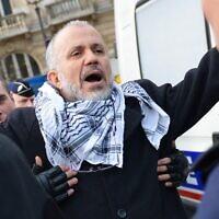Abdelhakim Sefrioui, président du collectif Cheikh Yassine, lors de son arrestation par des CRS après une manifestation pro-palestinienne non autorisée à Paris, le 29 décembre 2012. (Miguel MEDINA / AFP)