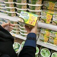 Une femme tient une boite de labneh turc dans un supermarché de Ryad, en Arabie saoudite, le 18 octobre 2020.(Crédit : FAYEZ NURELDINE / AFP)