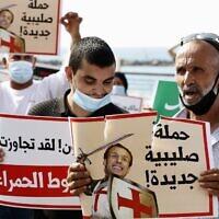Des manifestants arabes israéliens portant le masque pour cause de coronavirus tiennent des panneaux représentant le président français Emmanuel Macron sous les traits d'un chevalier médiéval des Croisades lors d'une manifestation contre la défense, par ce dernier, des caricatures de Mahomet, près de l'ambassade de France à Tel Aviv, le 27 octobre 2020. (Crédit :  JACK GUEZ / AFP)