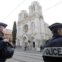 Des policiers français montent la garde sur le site d'une attaque au couteau à la Basilique Notre-Dame de Nice, le 29 octobre 2020. (Crédit : ERIC GAILLARD / AFP)