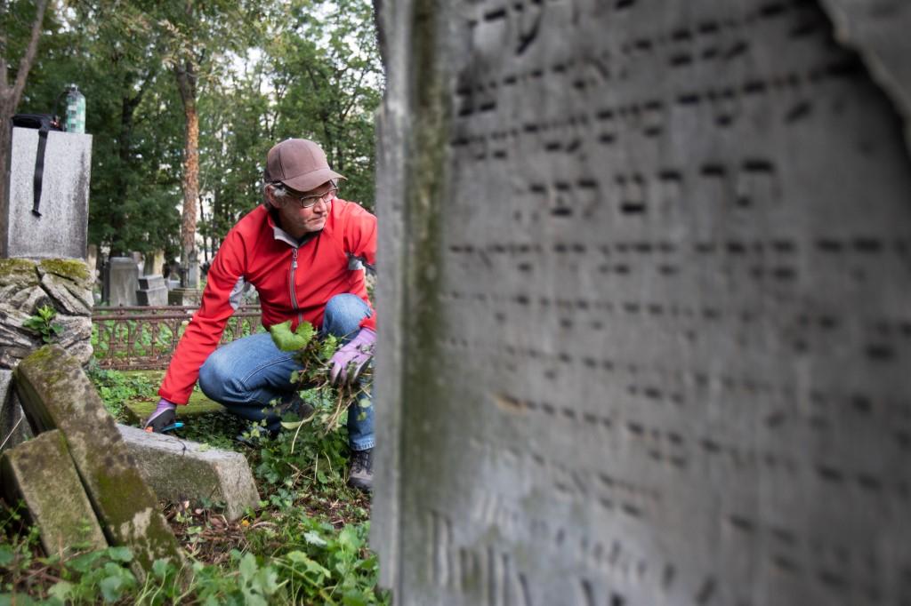Un bénévole nettoie l'ancien cimetière juif de Waehring, à Vienne, le 18 octobre 2020. (Crédit : ALEX HALADA / AFP)
