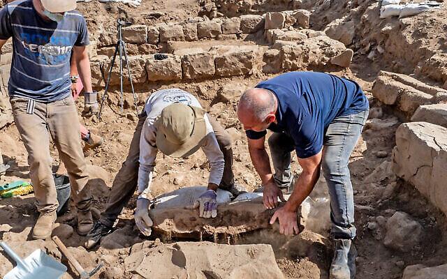 Des employés soulèvent la pierre de bornage découverte lors de fouilles de l'Autorité israélienne des Antiquités à Nafah, sur le plateau du Golan. (Crédit : Assaf Peretz/Autorité israélienne des Antiquités)