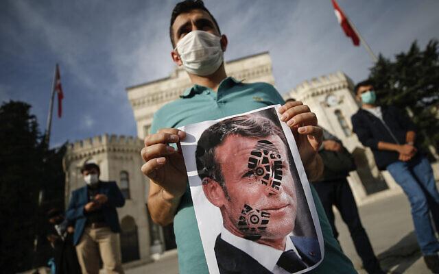 Un homme tient une photographie du président français Emmanuel Macron, piétinée lors d'une manifestation contre la France à Istanbul, le 25 octobre 2020. (Crédit : AP Photo/Emrah Gurel)