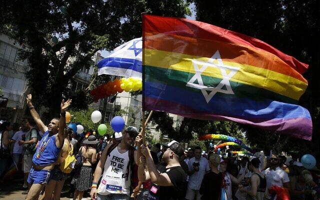 Des Israéliens et des touristes brandissent des drapeaux à la Gay Pride de Tel Aviv, le 8 juin 2018. (Crédit : AP/Sebastian Scheiner)