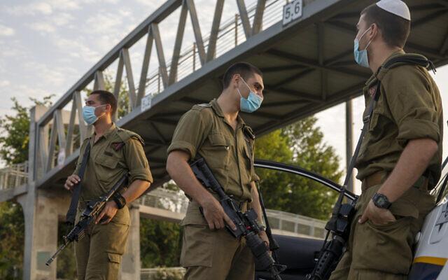 Des soldats israéliens portent le masque à un barrage routier à Tel Aviv, pendant le confinement national dû à la crise du coronavirus, le 19 septembre 2020 (Crédit : AP Photo/Ariel Schalit)