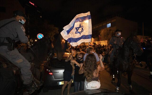 Des agents de police israéliens à cheval bloquent des manifestants lors d'une manifestation des Israéliens contre les mesures de confinement qui, selon certains, visant à limiter le mouvement de protestation anti-Netanyahu, à Tel Aviv,  le 1er octobre 2020 (Crédit :  AP Photo/Sebastian Scheiner)