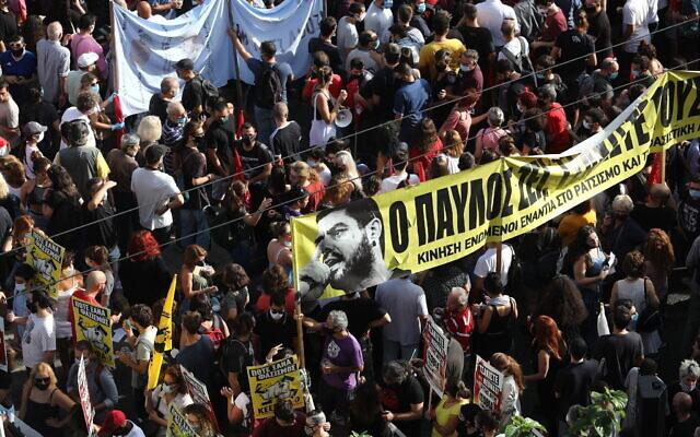Des manifestants brandissent une bannière dépeignant le chanteur grec de rap Pavlos Fyssas, poignardé et tué par un partisan de la formation d'extrême-droite Aube dorée en 2013, aux abords du tribunal, avant le verdict qui sera rendu dans l'affaire, le 7 octobre 2020. (Crédit :  AP Photo/Yorgos Karahalis)