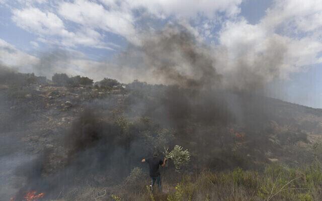 Des Palestiniens luttent contre un incendie qui aurait été entraîné par des bonbonnes de gaz lacrymogène lancées par des soldats Israéliens qui tentaient d'empêcher des manifestants d'atteindre un avant-poste israélien, à Beit Dajan, à l'est de Naplouse, en Cisjordanie, le 9 octobre 2020. (Crédit :AP Photo/Nasser Nasser)