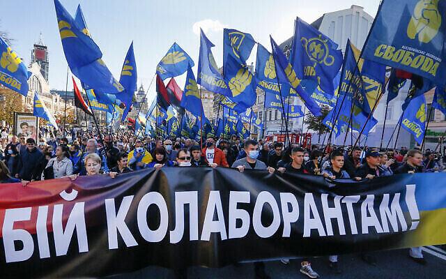 """Des manifestants brandissent le drapeau du parti d'extrême droite Svoboda et une banderole disant """"Combattre les collaborateurs !"""" lors d'un défile marquant le Jour du Défenseur de l'Ukraine, à Kiev, le 14 octobre 2020. (AP Photo/Efrem Lukatsky)"""