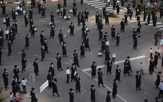 Des Juifs ultra-orthodoxes portent des masques et respectent la distanciation sociale pendant une manifestation organisée à Arad contre ce qu'ils considèrent être des incitations contre leur ville située au sud d'Israël, le 19 octobre 2020. (Crédit : AP/Oded Balilty)