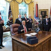 Le président américain Donald Trump après avoir terminé un appel téléphonique avec les dirigeants du Soudan et Israël, alors que le secrétaire au Trésor Steven Mnuchin, deuxième à gauche, le secrétaire d'Etat Mike Pompeo, le haut-conseiller à la Maison Blanche Jared Kushner, le conseiller à la sécurité nationale Robert O'Brien et d'autres applaudissent dans le bureau ovale de la Maison Blanche, à Washington, le 23 octobre 2020. (Crédit :  AP Photo/Alex Brandon)