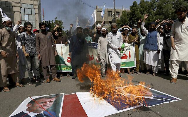 Des partisans de l'Organisation des étudiants musulmans brûlent le drapeau national français et vandalisent des images du président Emmanuel Macron pendant une manifestation contre le président et contre la publication des caricatures du prophète Mahomet qu'ils considèrent comme blasphématoires à Karachi, au Pakistan, le 30 octobre 2020. (Crédit : AP Photo/Fareed Khan)