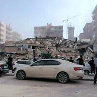 Des personnes travaillent sur un bâtiment effondré, à Izmir, Turquie, le 30 octobre 2020, après qu'un fort tremblement de terre en mer Egée ait secoué la Turquie et la Grèce (Crédit : DHA via AP)