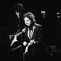 Le chanteur Bob Dylan sur la scène du Madison Square Garden de New York, le 30 janvier 1974, lors de l'une de ses trois apparitions avec The Band à New York. Robbie Robertson, à gauche, accompagne Dylan à la guitare. (Crédit : AP / Ray Stubblebine)