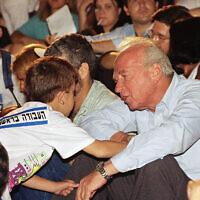 Un enfant serre la main de Yitzhak Rabin, chef du Parti travailliste israélien, lors d'un rassemblement électoral tenu le 20 juin 1992 à Tel Aviv, quelques jours avant la victoire électorale de Rabin. (AP Photo/Nati Harnik)
