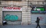 Un homme passe devant des magasins fermés dans la rue Jaffa, à Jérusalem, le 25 mars 2020. (Crédit : Yonatan Sindel/Flash90)