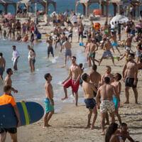 Les Israéliens profitent de la plage de Tel Aviv, alors que la température monte à 40 degrés dans certaines parties du pays, le 16 mai 2020. (Miriam Alster/Flash90)