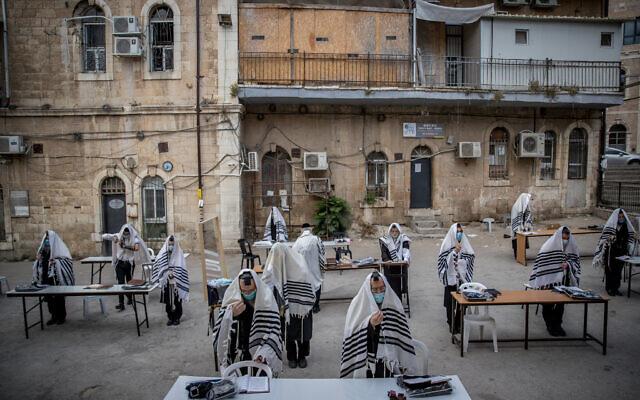Des Juifs ultra-orthodoxes de la dynastie hassidique Karlin prient en respectant les règles de distanciation sociale devant leur synagogue à Jérusalem, le 10 août 2020. (Yonatan Sindel/Flash90)