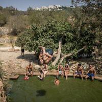 Les gens profitent d'une chaude journée d'été à la source Ein Lavan dans les montagnes de Jérusalem, le 30 août 2020. (Yonatan Sindel/Flash90)