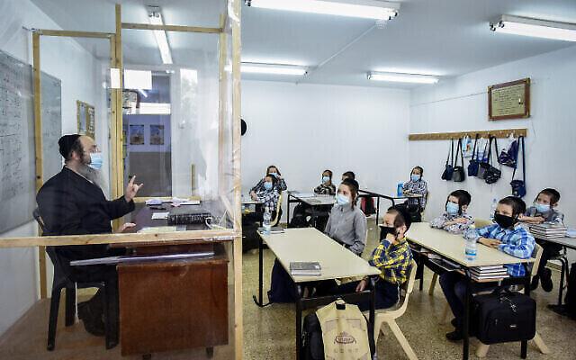 Des enfants ultra-orthodoxes du mouvement hassidique Kretchnif portent le masque en écoutant leur professeur dans une classe de la ville de Rehovot, le 10 septembre 2020. (Crédit : Yossi Zeliger/Flash90)