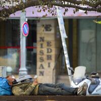 Un homme dort sur un banc public près de magasins fermés dans la rue Hillel, au centre de Jérusalem, pendant le confinement national, le 23 septembre 2020. (Crédit : Nati Shohat/Flash90)