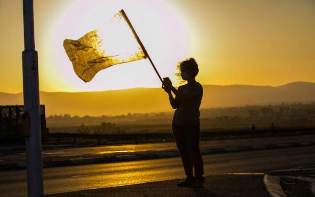 Une manifestante agite un drapeau dans la vallée de Jezreel, au nord d'Israël, le 26 septembre 2020. (Anat Hermony/Flash90)