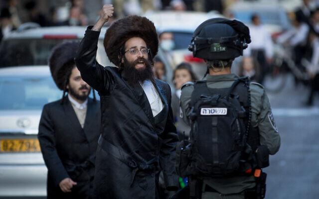 La police fait face à des hommes juifs ultra-orthodoxes lors d'une manifestation contre l'application des règlements d'urgence relatifs au coronavirus, dans le quartier de Mea Shearim, à Jérusalem, le 4 octobre 2020. (Nati Shohat/Flash90)