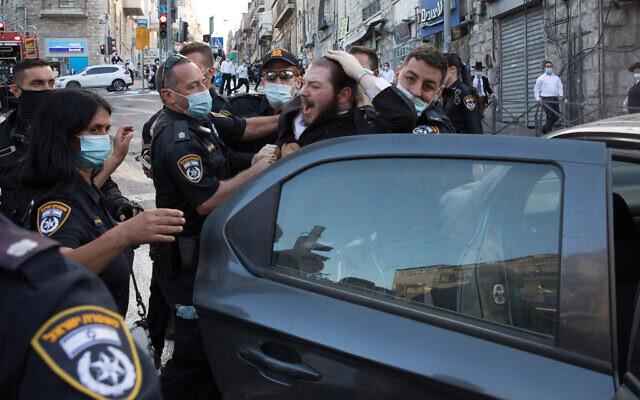 Des agents de police israéliens affrontent des manifestants ultra-orthodoxes pendant un rassemblement dénonçant les règles entraînées par le coronavirus dans le quartier de Mea Sharim, à Jérusalem, le 4 octobre 2020 (Crédit : (Nati Shohat/Flash90)